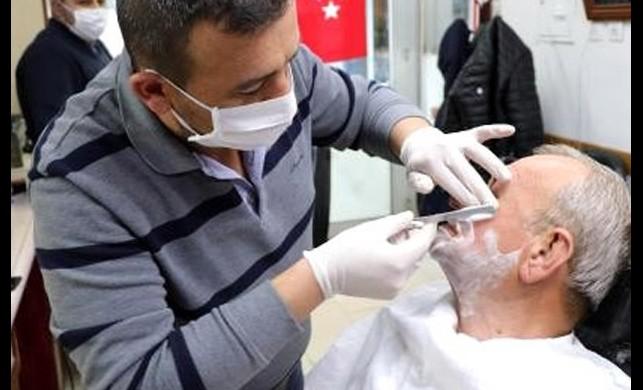 Koronavirüs tedbirleri! Berber maske ve eldiven takarak müşterilerini tıraş etmeye başladı